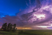 June 20, 2014 - A massive thunderstorm moves across the northern horizon lit internally by lightning. The clear sky behind it is lit blue from the perpetual twilight of summer solstice.