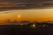 June 26, 2017 - The waxing crescent moon setting over a nearby farm. Shot at the start of a time-lapse sequence in Alberta, Canada, as the moon appeared from beneath an otherwise very cloudy sky. The dark side of the moon is lit by Earthshine, prominent despite the moon's low altitude and bright twilight sky.