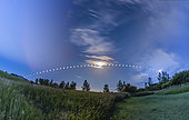 A multiple exposure composite showing the arc of the full moon of July 9/10, 2017 low across the southern sky on a summer night from dusk to dawn in Alberta, Canada. This illustrates the low arc of the moon across the sky in northern summer, from southeast at left to southwest at right. . . The sky is a blend of three long exposures:. a) the dusk 10 p.m. sky (left) with crepuscular rays in the clear twilight, . b)the 2 a.m. middle-of-the-night sky with the moon nearly due south (middle) with stars and iridescent colors around the moon in light cloud, . c) the dawn 5 a.m. sky (right) with increasing clouds hiding the moon.