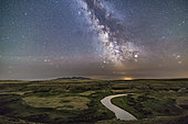 July 24, 2017 - The summer Milky Way over the winding Milk River at Writing-on-Stone Provincial Park, Alberta, Canada, on a slightly hazy night. The hills in the distance are the Sweetgrass Hills of Montana. The Park preserves ancient petroglyphs carved on the sandstone rock formations. It is a UN World Heritage Site, and is a sacred site to the Blackfoot First Nations people. Across the river are the preserved wood buildings of the 1880's NWMP Outpost. . . Sagittarius is in the thin cloud on the horizon, while the bright object is a hazy Saturn. Altair is the bright star at top of frame. Capricornus is rising at left. Light pollution from towns in Montana and from natural airglow color the sky.