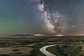July 25, 2017 - This is the Milky Way and night sky on a perfectly clear night, on the Canadian Prairies at Writing-on-Stone Provincial Park in Alberta, Canada, near the border looking south to the Sweetgrass Hills (West Butte) of Montana. The Milk River, which flows into the Missouri River, winds below. The site is sacred to the Blackfoot First Nations. . . The wooden buildings below are replicas of the late 1800s North West Mounted Police outpost in Police Coulee. . . Sagittarius and Scorpius are on the southern horizon, and Saturn is the bright object in the Dark Horse right of centre. The galactic centre is amid the bright star clouds above the horizon. The sky at left is green with natural airglow. . . The ground is illuminated only by starlight and airglow.