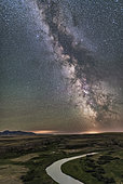 July 25, 2017 - The Milky Way and night sky on a perfectly clear night on the Canadian Prairies at Writing-on-Stone Provincial Park in Alberta, Canada, near the border looking south to the Sweetgrass Hills (West Butte) of Montana. The Milk River, which flows into the Missouri River, winds below. The site is sacred to the Blackfoot First Nations. . . The wooden buildings below are replicas of the late 1800s North West Mounted Police outpost in Police Coulee. . . Sagittarius and Scorpius are on the southern horizon at right, and Saturn is the bright object in the Dark Horse at far right. The galactic centre is amid the bright star clouds above the horizon. The sky at left is green with natural airglow. Altair is the bright star at top. . . The ground is illuminated only by starlight and airglow.