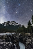 October 22, 2016 - The Pleiades star cluster and the other stars of Taurus rising above Mount Kerkeslin at Athabasca Falls, in Jasper National Park, Alberta, Canada. The sky is brightening with the rising waning moon off frame at left. Some cloud adds star glows and hazy patches to the sky.