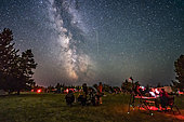 A Perseid meteor streaks down the Milky Way over the Saskatchewan Summer Star Party in the Cypress Hills of southwest Saskatchewan, Canada. The Milky Way shines to the south. . . Observers enjoy their views of the sky at left while an astrophotographer attends to his camera control computer at right.