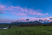 June 17, 2018 - A photographer at Waterton Lakes National Park, at Maskinonge, in the evening twilight, with the clouds lit by the setting Sun.