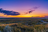 August 26, 2019 - A sunset twilight tinted with volcanic ash high in the atmosphere adding the purple glow, taken at Grasslands National Park from the 70 Mile Butte trail in Saskatchewan, Canada.