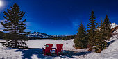 March 18, 2019 - Iconic red chairs under a moonlit winter sky at frozen Two Jack Lake, Banff National Park, Canada, with Orion and Canis Major over Mount Rundle to the south. Sirius is the bright star over Mount Rundle. . . A gibbous moon can be seen illuminating the scene just at the frame edge.