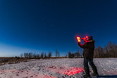 Astronomer using binoculars and guidebook to find targets in the night sky. Taken under the light of a full moon with Orion and Sirius to the south.