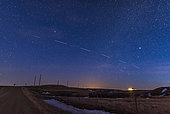 A pass of the Starlink 4 train of satellites on March 26, 2020. This was the set launched February 17, 2020. At left they can be seen dimming as they enter Earth's shadow. They paraded across the sky over many minutes, each disappearing to the south. The stars are pinpoints but the satellites are streaks because of their motion over the length of the 13-second exposure. . This view is looking southwest. Sirius is at right; Alphard in Hydra is at upper left.