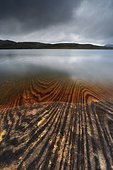 Geology lines in Sandvannet Lake, Nordland County, Norway. The Glomfjord Mountains are visible on the horizon.