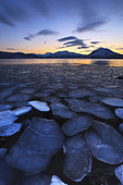 A rare sight in Tjeldsundet, Troms County, Norway. Ice flakes drifting in the sunset looking towards the mountains on Tjeldoya Island.