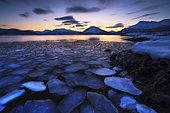 Ice flakes drifting against the sunset in Tjeldsundet strait, Troms County, Norway.