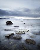 Long exposure scene of rocks in Vaagsfjorden fjord, Skanland, Troms, Norway.