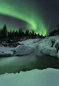 A wintery waterfall and aurora borealis over Tennevik River, Troms, Norway.