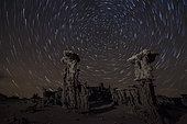 Intricate sand tufa formations backdropped by star trails at Mono Lake, California.