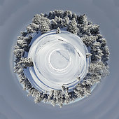 Planet of beautiful fir trees covered with snow in the Jura Mountains on a winter day in Switzerland.
