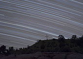 Star trails created by the Earth's spin arch over a cross on the hill at Camp Billy Joe, Oklahoma.