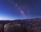 The rising sun begins fading away the nightime Milky Way over the needle rock formations of Bryce Canyon, Utah.