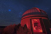 An astronomer peers through a telescope at the Orion region of the sky through thin clouds near Crowell, Texas.