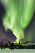 Aurora borealis and the Big Dipper light up the sky above a log cabin at Whitehorse, Yukon, Canada.