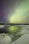 Aurora borealis and Venus setting over a mountain and creek by Fish Lake, Whitehorse, Yukon, Canada.