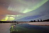 Aurora borealis over creek by Fish Lake, Whitehorse, Yukon, Canada.