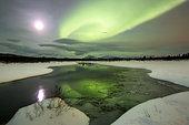 Aurora borealis and full moon setting over a mountain and creek by Fish Lake, Whitehorse, Yukon, Canada.