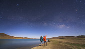 A couple of lovers enjoy a romantic moment under the Milky Way on a moonlit night in Tibet, China.