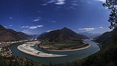 Moonlight on the Yangtze River in China. Yangtze River, the third longest river in the world, runs from the Qinghai-Tibet Plateau, surges southeastward until it meets the Hengduan Mountain Range. The unusual geological phenomenons force the Yangtze to make a sudden V-shaped bend and flow to the northeast. This extraordinary turn, nearly 180-degrees, is called First Bend of the Yangtze River. In the sky is the northern stars, from the Cassiopeia at left to Little Dipper and Polaris (the North Star) at top middle and the seven prominent stars of the Big Dipper at right.