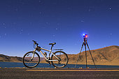 Night adventure with a camera, tripod and bicycle at Yamdrok Lake, Tibet, China, in a full moon night.