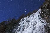 Stars of the Winter Triangle shine above an icefall on a moonlit night in the Sichuan province of China.