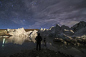 The night sky above a glacier in the Himalayas of Tibet, on the border of China and Bhutan. The photographer made a self-portrait in front of the ice lake.