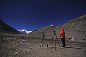 A photographer is capturing the moonlight landscape of Mount Everest, the top of the world.