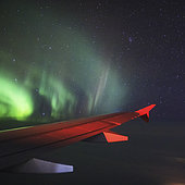 Aurora borealis dances outside of an airplane's passenger window from Moscow to Murmansk, with the Beehive Cluster visible on the upper right.