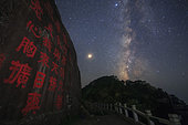 The Milky Way shines above a stone inscription at Mount Jiuhua in Anhui province of China. Mount Jiuhua is one of the four sacred mountains of Chinese Buddhism. It is famous for its rich landscape and ancient temples. The bright planet Mars is visible on left side of Milky way.