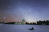 A stargazer sits in the snow to view the winter Milky Way and zodiacal light at Nanshan observatory near Urumchi, Xinjiang, China.