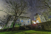 Star trails around the northern celestial pole above a castle in Wolfsberg, Germany.