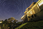 Star trails around the northern celestial pole above a house in California, USA.
