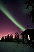 Aurora borealis above cabin on shoreline of Great Slave Lake, Yellowknife, Northwest Territories, Canada.