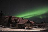 Aurora borealis over a cabin, Yellowknife, Northwest Territories, Canada.