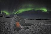 Aurora borealis over an igloo on Walsh Lake, Yellowknife, Northwest Territories, Canada.