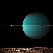 An artist's depiction of a ringed gas giant planet surrounded by it's moons. The view is from the surface of one of the rocky airless moons.