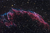 The Veil Nebula, also known as the Cygnus Loop or the Witch's Broom Nebula, is a large, relatively faint supernova remnant in the constellation Cygnus. When finely resolved, some parts of the image appear to be rope like filaments. The standard explanation is that the shock waves are so thin, less than one part in 50,000 of the radius, that the shell is only visible when viewed exactly edge-on, giving the shell the appearance of a filament. Undulations in the surface of the shell lead to multiple filamentary images, which appear to be intertwined.