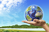 Human hand holding Earth globe with a beautiful green landscape and river background.