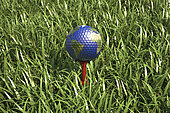 3D rendering of an Earth golf ball on tee in the grass, close-up.