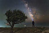 Explorer standing on the coast of the Black Sea with the Milky Way and light trails of cars from the top of the mountain Ilyas-Kaya in Crimea.