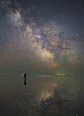 Man stands alone on Lake Elton in Russia under the center of the Milky Way and the stars reflected in the lake.