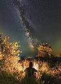Man sitting near the campfire in the forest under the stars and the Milky Way, Sudak, Crimea.