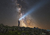 Man standing on the rocks of Lago-Naki plateau and shining a flashlight on the Milky Way, Russia.