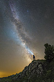 Man standing on a mountain top and shining a flashlight on the Milky Way, Russia.